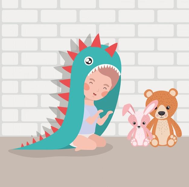 Weinig babyjongen met gevuld speelgoed en kostuum