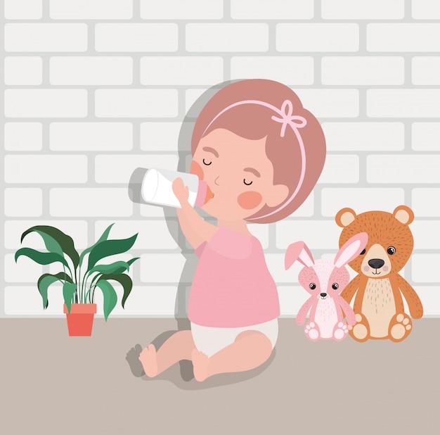 Weinig babymeisje met flessenmelk en gevuld speelgoedkarakter