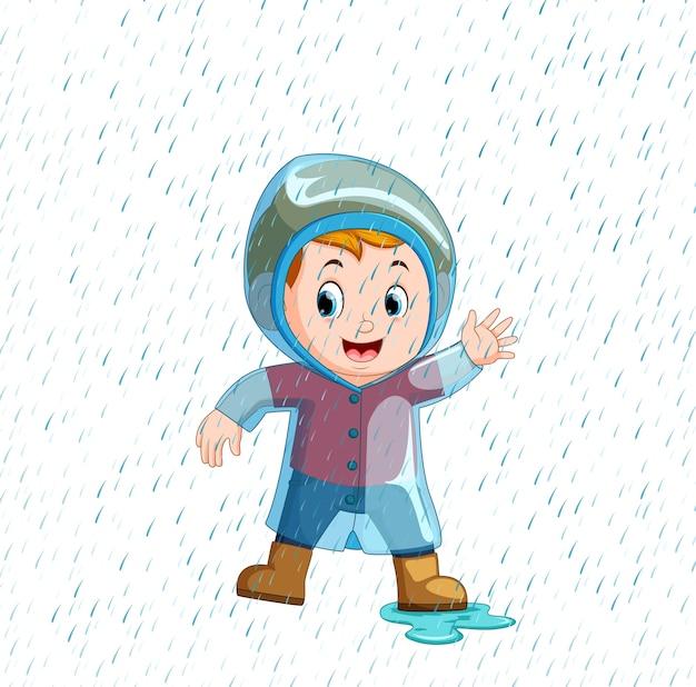 Weinig jongen die blauwe regenjas en zware regen draagt