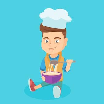 Weinig kaukasische jongen die in chef-kokhoed het deeg maakt.