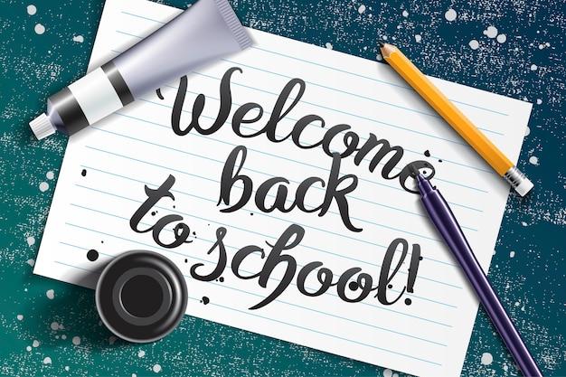 Welkom terug op school handgetekende letters met kalligrafie mockup met penseel pen, scherp potlood, verf tube en zwarte inktfles op de ruimte van wit vel papier en grunge krijtbord
