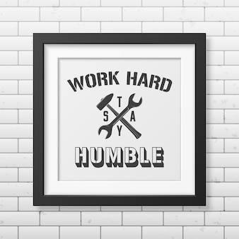Werk hard, blijf nederig - citeer typografische achtergrond in realistisch vierkant zwart frame op de bakstenen muurachtergrond.