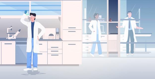 Wetenschapper die in medische laboratoriumonderzoekers in witte jassen werkt die chemische experimenten maken
