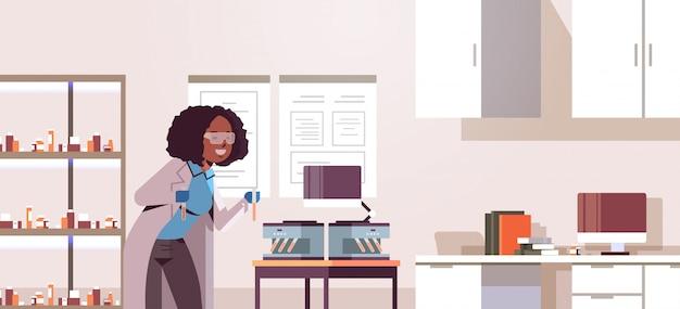 Wetenschapper met reageerbuisjes met bloedmonsters, afro-amerikaanse vrouw in uniform met behulp van analysator medische machine