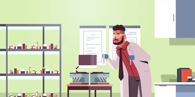 Wetenschapper met reageerbuisjes met bloedmonsters, man in uniform met behulp van analysator medische machine