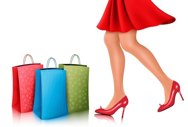 Winkelende vrouw die rode kleding en hoge hielschoenen met het winkelen zakken draagt.