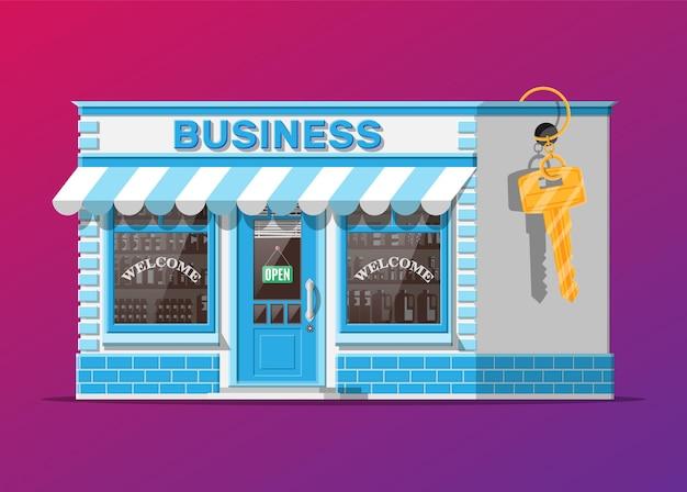 Winkelpand of bedrijfspand met sleutel. promotie van onroerend goed, opstarten. nieuwe zaken verkopen of kopen. kleine winkel in europese stijl aan de buitenkant.