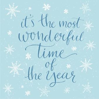 Winter inspirerende quote voor kaarten, posters en social media content. het is de mooiste tijd van het jaar. moderne kalligrafie op blauwe achtergrond met witte sneeuwvlokken.