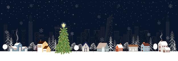 Winterlandschap in de stad 's nachts met sneeuw vallen op kerstavond.