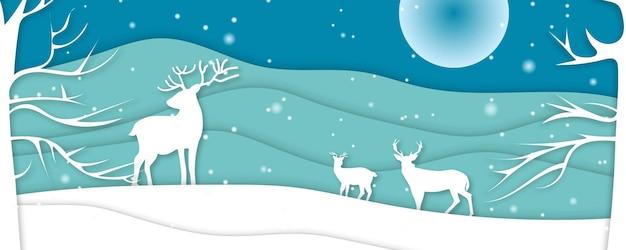 Winterlandschap met uitgesneden hertenpapier en dennenbomen in de sneeuw. feestelijke horizontale banner met tekst merry christmas, village en vliegende santa's slee in de nachtelijke hemel met sterren, sneeuwval en maan.