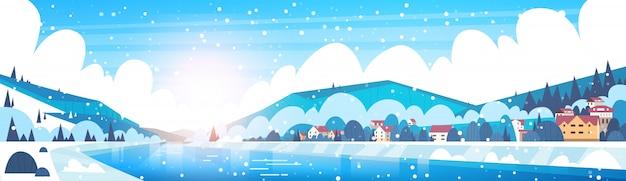 Winterlandschap van kleine dorpshuizen aan de oevers van bevroren rivier en bergheuvels bedekt