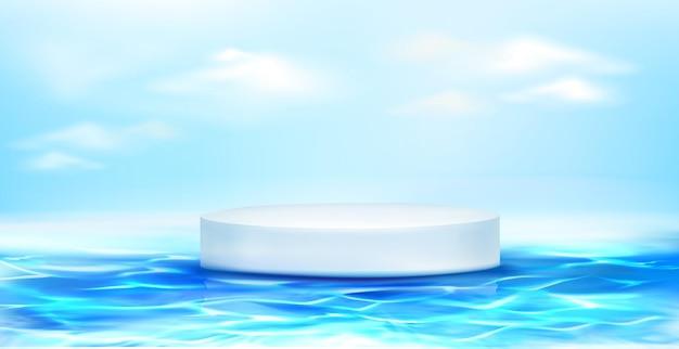Wit rond podium dat op blauwe waterspiegel drijft.