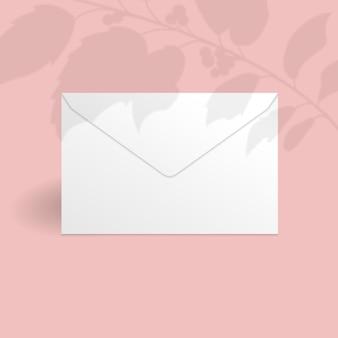 Witte envelop sjabloon met hulst bessen tak met bladeren overlay schaduw.