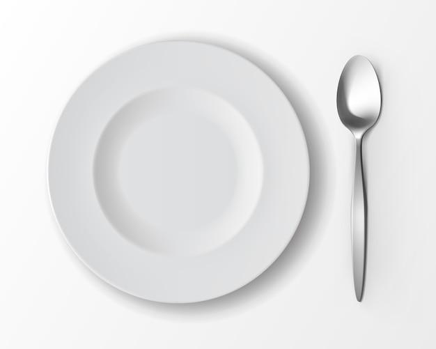 Witte lege ronde soepplaat met zilveren tafellepel