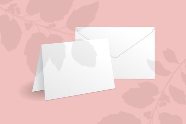 Witte staande kaart en envelop sjabloon met hulst bessen tak met bladeren overlay schaduw.