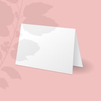 Witte staande kaartsjabloon met holly berry tak met bladeren overlay schaduw.