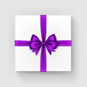 Witte vierkante geschenkdoos met glanzend paars lint, bovenaanzicht
