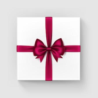 Witte vierkante geschenkdoos met glanzende bourgondische rode wijn satijn boog en lint bovenaanzicht close-up geïsoleerd op een witte achtergrond