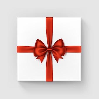 Witte vierkante geschenkdoos met glanzende rode satijnen boog en lint bovenaanzicht close-up geïsoleerd op een witte achtergrond