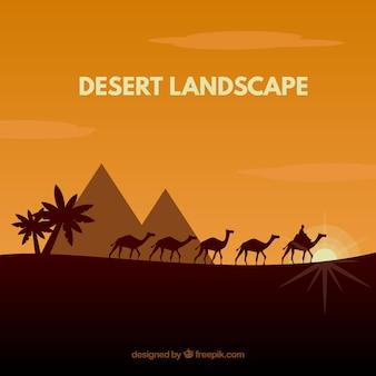 Woestijnlandschap met piramides en caravan