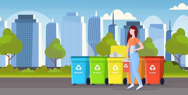 Womanputting emmer met papierafval in container verschillende soorten recycling bakken gescheiden afval sorteren beheer concept modern stadsgezicht achtergrond vlak horizontaal volledige lengte