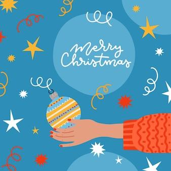 Xmas wenskaart versierd met confetti, kerstbal in menselijke hand. vrouwelijke hand versieren of kerstboomversiering vasthouden. vectorillustratie platte cartoon.
