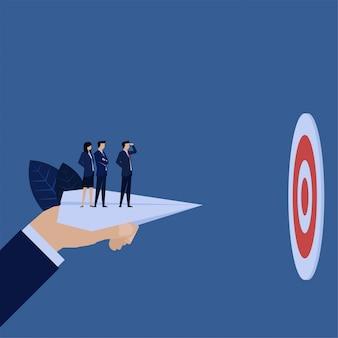 Zakelijke hand houden papieren vliegtuig en team erboven kijken doel.