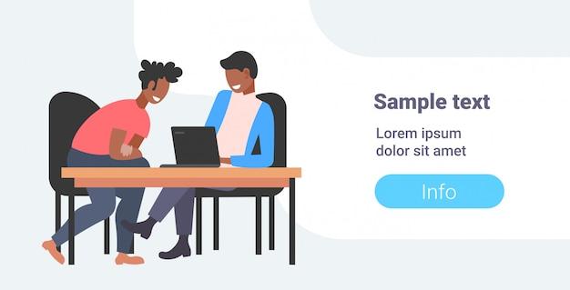 Zakenlieden collega's zitten op de werkplek bureau twee zakenlieden met behulp van laptop werkproces teamwork concept horizontale volledige lengte kopie ruimte