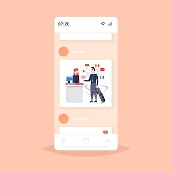 Zakenman aankomen bij hotel receptie man inchecken met mobiele app woordenboek of vertaler bespreken met receptioniste verbinding concept verschillende talen vlaggen smartphone scherm van volledige lengte