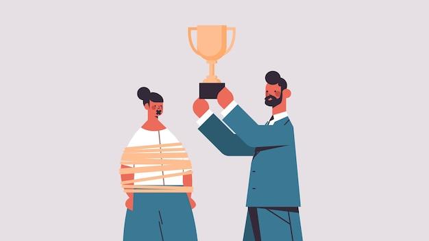 Zakenman bedrijf trofee beker in de buurt van gebonden zakenvrouw met duct tape op de mond genderongelijkheid seksisme discriminatie portret