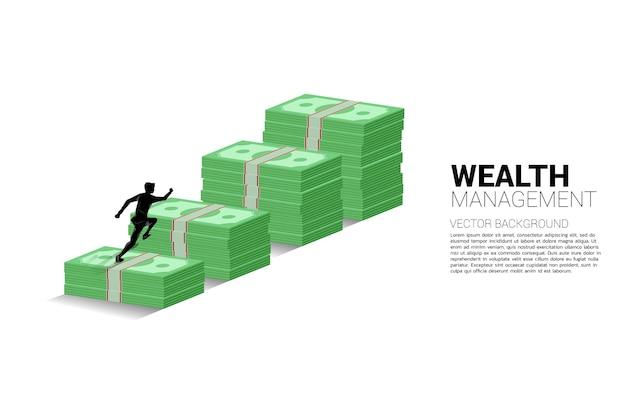 Zakenman die bovenop de groeigrafiek met stapel bankbiljetten loopt