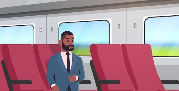 Zakenman die door de mens van de treinpassagier reizen in kostuumzitting op comfortabele stoel tijdens zakenreisreis het portret van het korte afstands openbaar vervoerconcept horizontaal