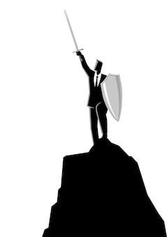 Zakenman die een zwaard en een schild bovenop rots opheft