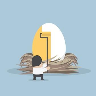 Zakenman die gouden kleur op het ei schildert
