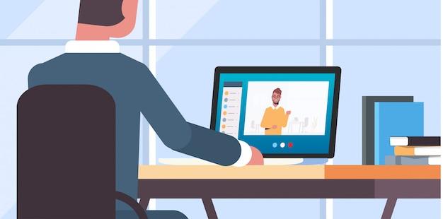 Zakenman die laptop met behulp van op werkplaats videogesprek met mannelijk communicatie van het collega sociaal netwerk concept