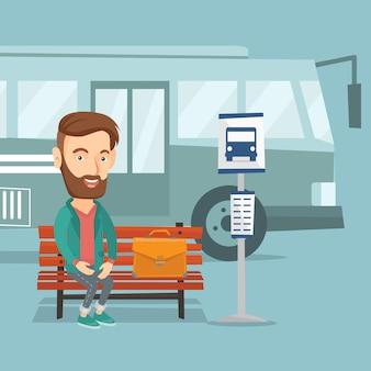 Zakenman die op bus bij de bushalte wachten.
