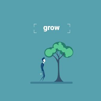 Zakenman die zich onder groen de groeiontwikkelingconcept bevinden van de boominvestering