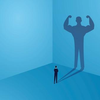 Zakenman die zijn eigen sterke persoonlijkheidsschaduw bekijken op muur, binnenmachtsconcept