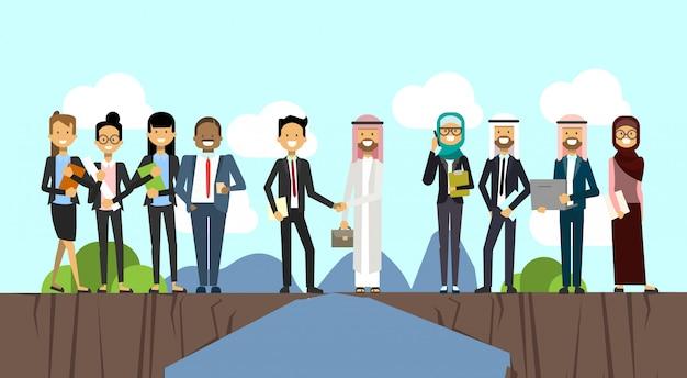 Zakenman in pak handen schudden arabische man traditionele kleding kloof tussen bergen mix race volledige lengte zakelijke overeenkomst en partnerschap concept
