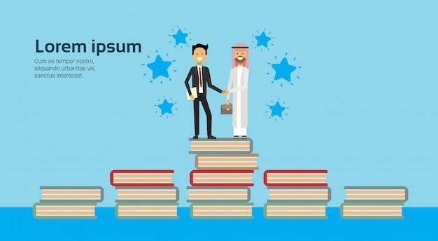 Zakenman in pak handen schudden arabische man traditionele kleding op boeken stapelen volledige lengte zakelijke overeenkomst en partnerschap concept