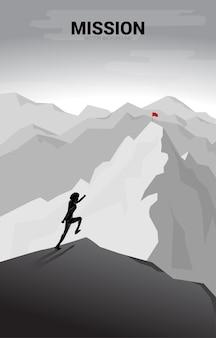 Zakenman loopt naar de vlag op de top van de berg.
