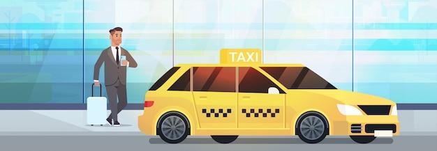 Zakenman met behulp van mobiele app taxi bestellen op straat zakenman in formele slijtage met bagage in de buurt van gele taxi stad transportdienst