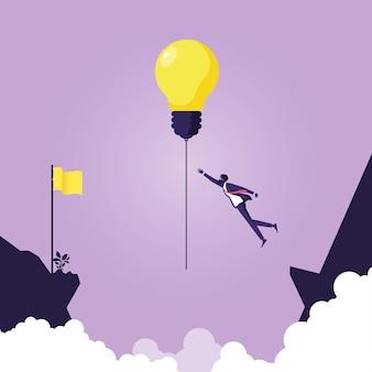 Zakenman probeert gloeilamp idee kruis over klif, symbool leiderschap te hangen