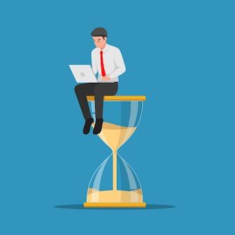 Zakenman werken met laptop zittend op grote zandloper. tijdbeheer en deadlineconcept