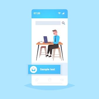 Zakenman zit op de werkplek bureau zakenman met behulp van laptop werkproces concept volledige lengte smartphone scherm mobiele applicatie