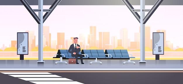 Zakenman zitten moderne bushalte zakenman met koffer wachten openbaar vervoer op de luchthaven station stadsgezicht