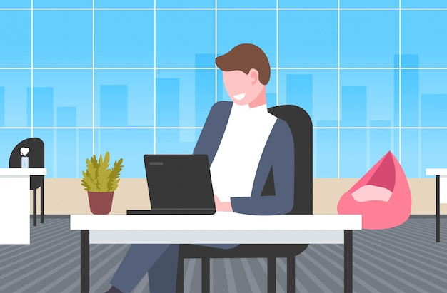 Zakenman zittend op de werkplek bureau zaken man met laptop werkproces concept moderne kantoor interieur horizontale portret