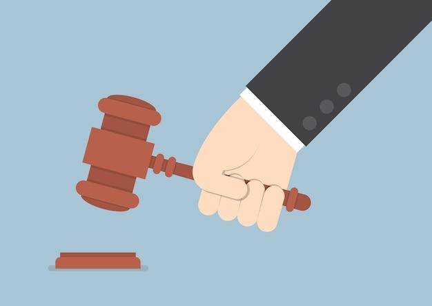 Zakenmanhand die de hamer van de rechter kloppen