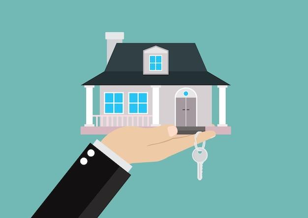 Zakenmanhand die het huis en de sleutels houden