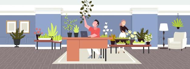 Zakenmanzitting op comfortabele werkplaats met groen het bureauconcept van de potplanten binnenlands atmosfeer
